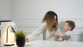 Chłopiec zatrzymuje jego mamy pracować podczas gdy dzwoni telefon w jej miejsce pracy w biurze matka pracuje zbiory