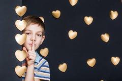Chłopiec zerkanie na złotych sercach Zdjęcie Royalty Free