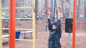Chłopiec zrozumienie na gimnastycznych pierścionkach w podwórzu miasto dom na boisku zbiory wideo