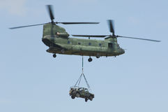 CH-47 Chinook helicopter. Carrying 4x4x off-road mercedes royalty free stock photo
