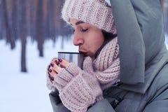 Chá calmo macio do gosto da jovem mulher do copo em uma floresta nevado Foto de Stock