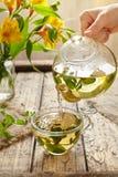 Chá da pastilha de hortelã que derrama no copo de vidro do bule na tabela Fotos de Stock