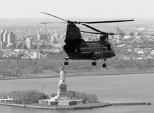 CH--46Eflyg i NYC med statyn av frihet i bakgrunden Arkivbilder