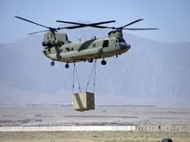 Sling Load Chinook. Heavy Hooker. CH-47F taking on a sling load in MEZ Afghanistan. Chinooks are known throughout the army as `Heavy Hookers` because of the Royalty Free Stock Photography