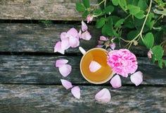 Ch? no estilo country no jardim do ver?o na vila Copo de Vintafe da tisana verde em placas de madeira resistidas e no rosa de flo imagem de stock royalty free