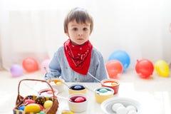 Chłopiec, barwi jajka dla wielkanocy Obrazy Royalty Free