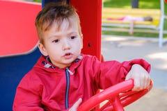 Ch?opiec bawi? si? na boiska samochodowym carousel w parku rozrywki obrazy royalty free