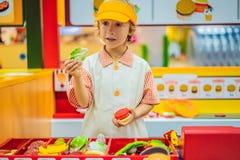 Ch?opiec bawi? si? w zabawkarskiej kuchni, gotuje hamburger fotografia royalty free