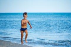 Chłopiec bieg przy brzeg blisko morza Zdjęcia Royalty Free