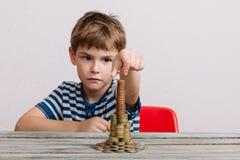 Chłopiec budynku sterta gotówka Fotografia Stock