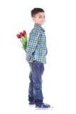 Chłopiec chuje kwiaty czerwoni tulipany za ja Zdjęcia Royalty Free