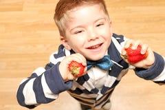 Chłopiec cztery roku trzyma truskawki Obrazy Stock