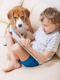 Chłopiec czytanie dla jego psa w domu Zdjęcie Royalty Free