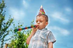 Chłopiec dmucha partyjnego róg Fotografia Royalty Free