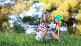 Chłopiec dmuchania barwiony pinwheel zbiory wideo