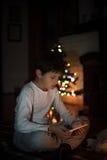 Chłopiec dopatrywania pastylka obok choinki a Obraz Royalty Free