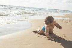 Chłopiec dotyka piasek w seashore Obraz Stock