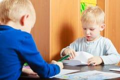 Chłopiec dzieci dzieciaki pisze na papierze. W domu. Obraz Royalty Free