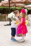 Chłopiec dzieciak daje kwiaty dziewczyny dziecko na urodziny Obraz Royalty Free