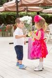 Chłopiec dzieciak daje kwiaty dziewczyny dziecko na urodziny Zdjęcie Stock