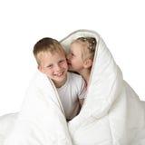 Chłopiec i dziewczyna szepcze pod koc Zdjęcie Stock