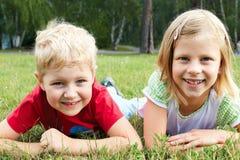 Chłopiec i dziewczyny lying on the beach na zielonej trawie Obraz Royalty Free
