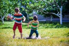 Ch?opiec i jego brat sztuka w lato parku Dzieci z kolorowymi ubraniami skacz? w ka?u?y i b?ocie w ogr?dzie obraz royalty free