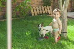 Chłopiec i jego pies w ogródzie Zdjęcie Royalty Free