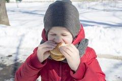 Chłopiec je hamburger plenerowego Fotografia Stock
