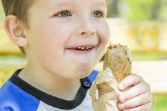Chłopiec je hot dog outdoors Obraz Royalty Free
