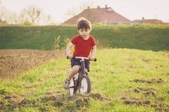 Chłopiec jedzie balansowego rower w wsi Obrazy Royalty Free