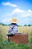 Chłopiec jest ubranym kowbojskiego kapeluszu obsiadanie na walizce Fotografia Royalty Free
