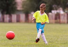 Chłopiec kopania futbol na sporta polu Fotografia Stock