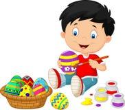 Chłopiec kreskówka maluje Wielkanocnego jajko Zdjęcia Royalty Free