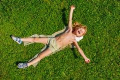 Chłopiec lying on the beach na trawie Zdjęcia Royalty Free