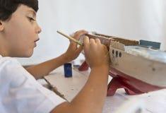 Chłopiec maluje starego drewnianego statek Fotografia Royalty Free