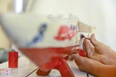 Chłopiec maluje starego drewnianego statek Fotografia Stock