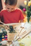 Chłopiec maluje Wielkanocnych jajka paintbrush Obrazy Stock
