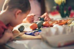 Chłopiec maluje Wielkanocnych jajka paintbrush Fotografia Royalty Free