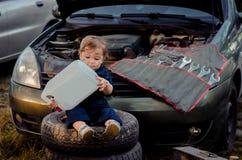 Chłopiec mechanik naprawia samochód obraz stock