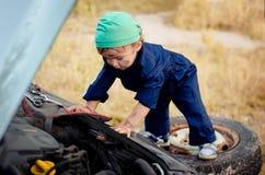 Chłopiec mechanik naprawia samochód obraz royalty free