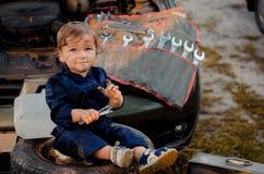 Chłopiec mechanik naprawia samochód fotografia royalty free