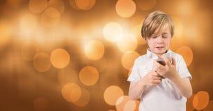 Chłopiec mienia telefon komórkowy nad bokeh Zdjęcia Royalty Free