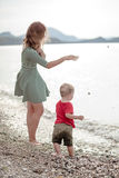 Chłopiec miotania otoczaki morze Zdjęcia Royalty Free