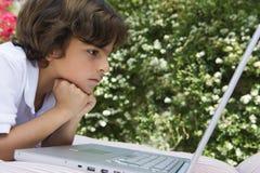 Chłopiec Patrzeje laptop Fotografia Stock