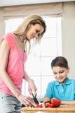 Chłopiec patrzeje macierzystego przecinania czerwonego dzwonkowego pieprzu w kuchni Zdjęcia Stock