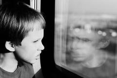 Chłopiec patrzeje przez okno Obrazy Royalty Free