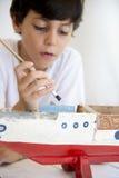 Chłopiec pianting starego drewnianego statek Zdjęcia Stock