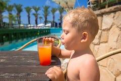Chłopiec pije sok przy basenem zdjęcia royalty free