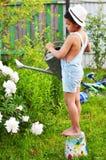 Chłopiec podlewanie kwitnie od podlewanie puszki w jego ogródzie w zdjęcia stock